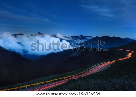 Motion blur of traffic on a winding road in the mountains. - stock photo