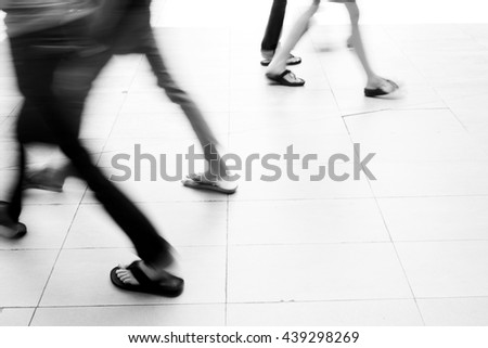 Motion blur people walking on white tiled floor. They are hurry in rush hour. - stock photo