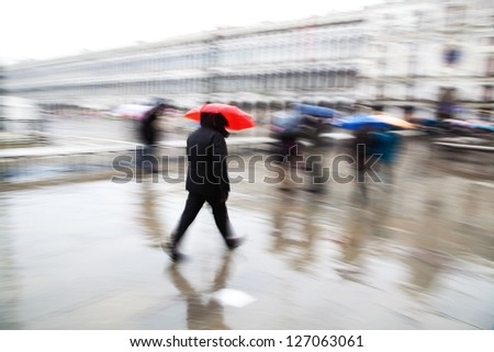motion blur picture of walking people on the St. Mark's Square in Venice on a rainy day