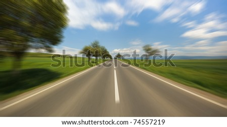 Motion blur road seen from fast moving car - stock photo