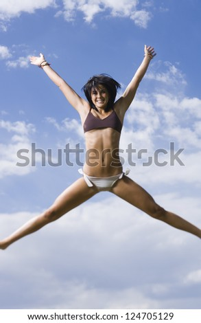 Motion blur shot of a woman in bikini jumping against sky