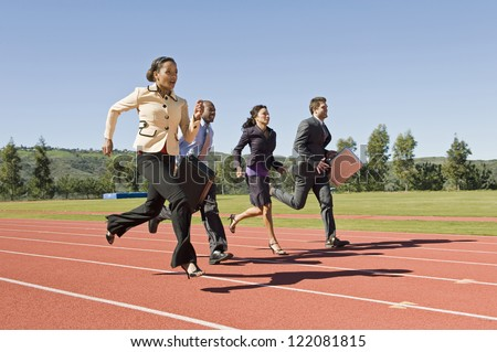 Motion blur shot of four business people running together on racing track - stock photo
