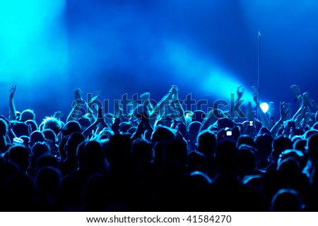 Motion Blur version of clapping hands/cheering crowd at concert - stock photo