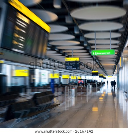 Motion blurred airport lounge with rushing people silhouettes in the end of corridor. Heathrow airport, Great Britain. - stock photo