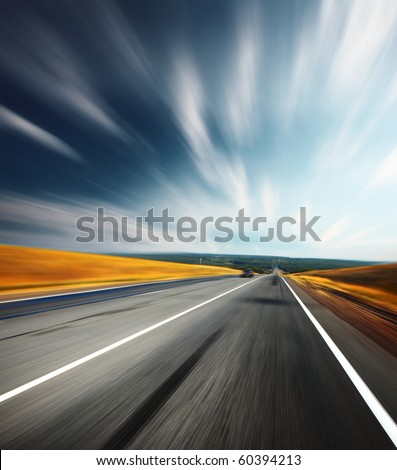 Motion blurred asphalt road and blurred sky with clouds