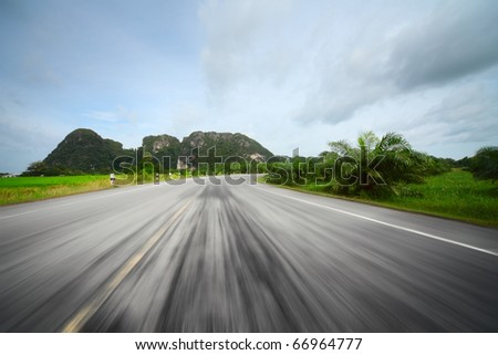 Motion blurred asphalt road and mountains on a horizon - stock photo