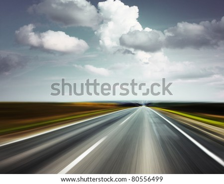 Motion blurred asphalt road and sky with clouds - stock photo