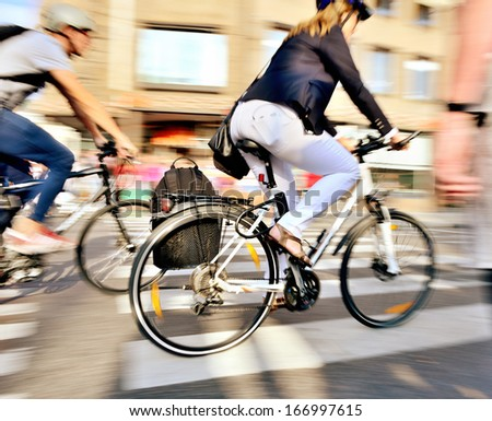 Motion blurred bicyclists on their home from work - stock photo