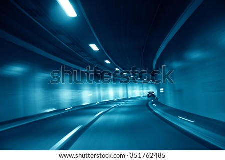 Motion blurred blue colored tunnel high speed car driving. Motion blur visualizes the speed and dynamics. Personal perspective used.  - stock photo