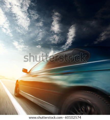 Motion blurred car on asphalt road - stock photo