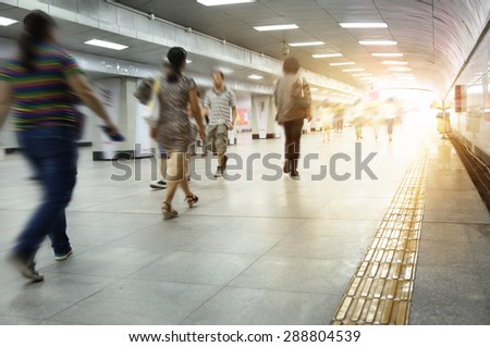 Motion blurred commuters walking in subway station.