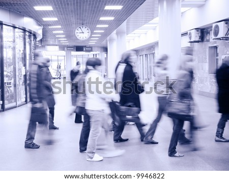 motion blurred crowd under clock - stock photo