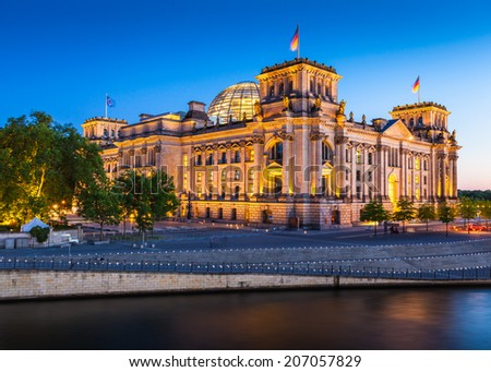 Motion blurred cruise boat passes in front of the mighty Reichstag parliament (1894) illuminated at night and reflected in the river Spree, Berlin, Germany. - stock photo
