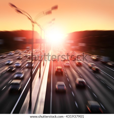 Motion blurred image of city traffic during sunset. - stock photo