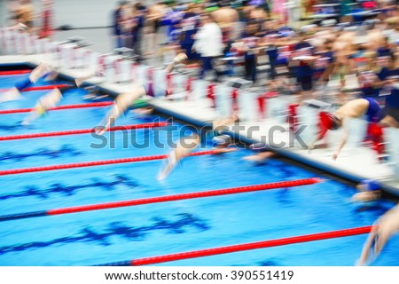 Motion blurred image of people diving into the pool at the start of a swimming race - stock photo