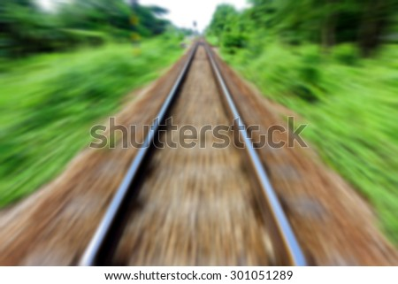 Motion blurred image of railway track on upcountry. - stock photo