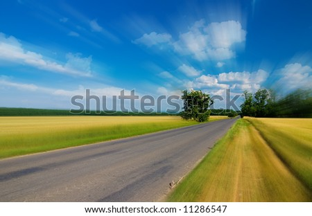 Motion blurred Landscape - road, field, trees and blue cloudy sky (ideal for background or wallpaper) - stock photo