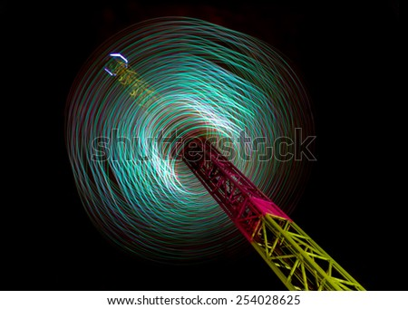 Motion blurred lights of a fairground carousel against a black background - stock photo