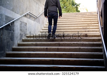 Motion blurred man walking the stairs into bright light - stock photo