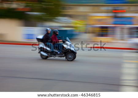 Motion Blurred moped moving past the camera - stock photo