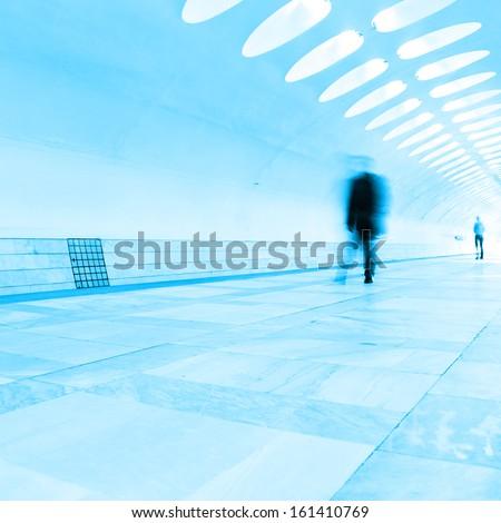 Motion blurred passenger walking in subway station. - stock photo