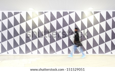Motion blurred pedestrian against patterned wall - stock photo