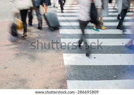 Motion blurred pedestrians crossing street