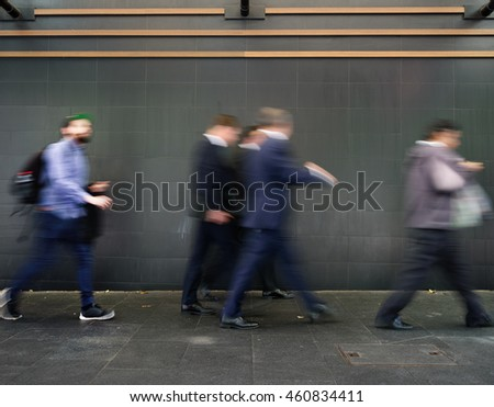 Motion blurred pedestrians on sidewalk