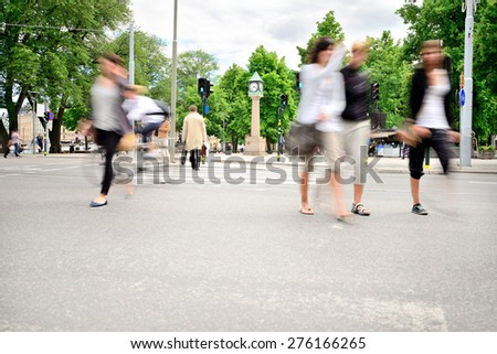 Motion blurred pedestrians on street - stock photo