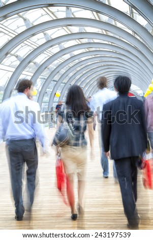 Motion blurred people in the office building - stock photo