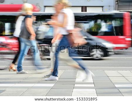 Motion blurred people on sidewalk - stock photo