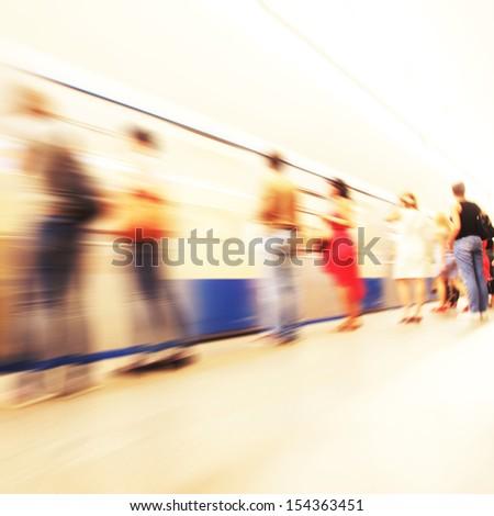 Motion blurred people waiting at  subway station. - stock photo