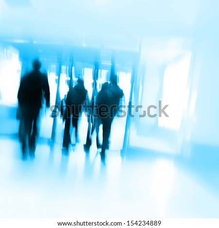 Motion blurred people walking at the modern building.  - stock photo