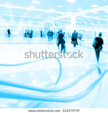Motion blurred people walking in airport. - stock photo