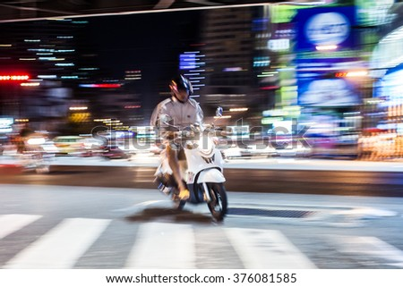 Motion blurred photo of a moped rider. - stock photo
