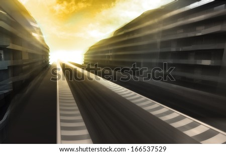 motion blurred racetrack in business city with orange sky wallpaper illustration - stock photo