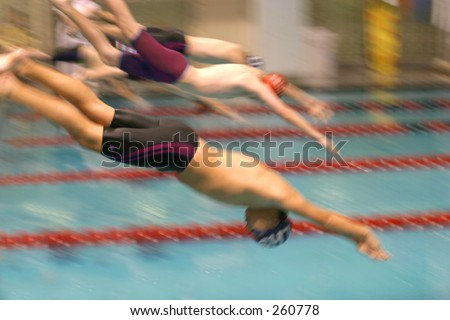 Motion blurred swimmers diving into a pool. - stock photo