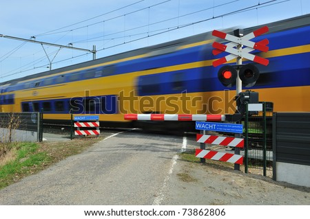 Motion blurred train passing a railroad crossing. Dutch signs warning not to cross and red lights flashing. - stock photo