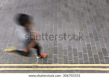 Motion blurred view of a man running. High angle view of a Asian man running on street. Male fitness concept.  