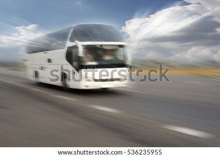 Motion blurred white bus on the highway on a background of the sun's rays through the clouds
