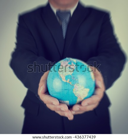 Motion blurry background Businessman Holding World Map Globe for Business and Technology concept.