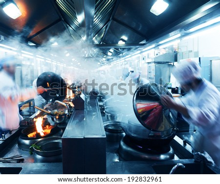 Motion chefs in a Chinese restaurant kitchen. - stock photo