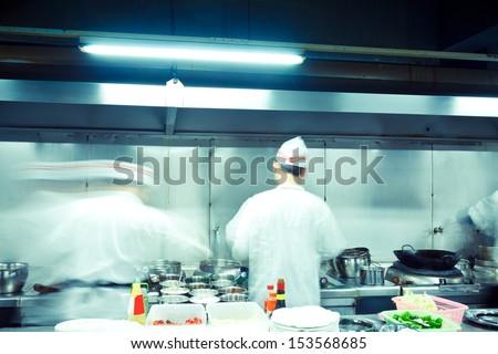 motion chefs of a restaurant kitchen - stock photo