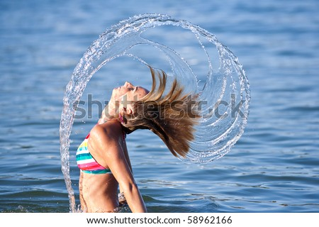 Motion freeze on a girl splashing the sea water with her hair