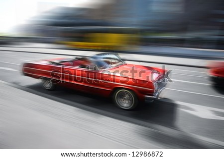 motion image. red retro car in the city - stock photo