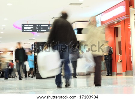 motion of busy shoppers in shopping mall - stock photo