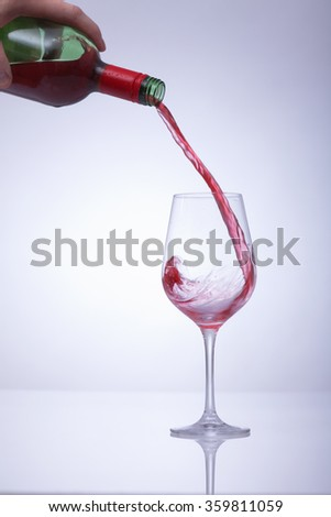Motion picture of a man hand fill a glass with wine. Against a white background and a vignette. - stock photo