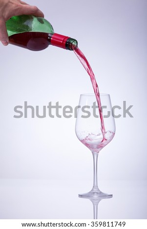 Motion picture of a man hand fill a glass with wine. Against a white background and a vignette.reflecting on the table. - stock photo