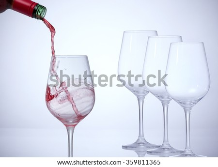 Motion picture of a man hand fill a glass with wine.Three empty glasses stand in a row.   Against a white background and a vignette. - stock photo
