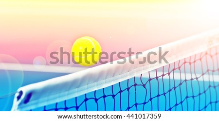 motion tennis ball over net with color filters - stock photo